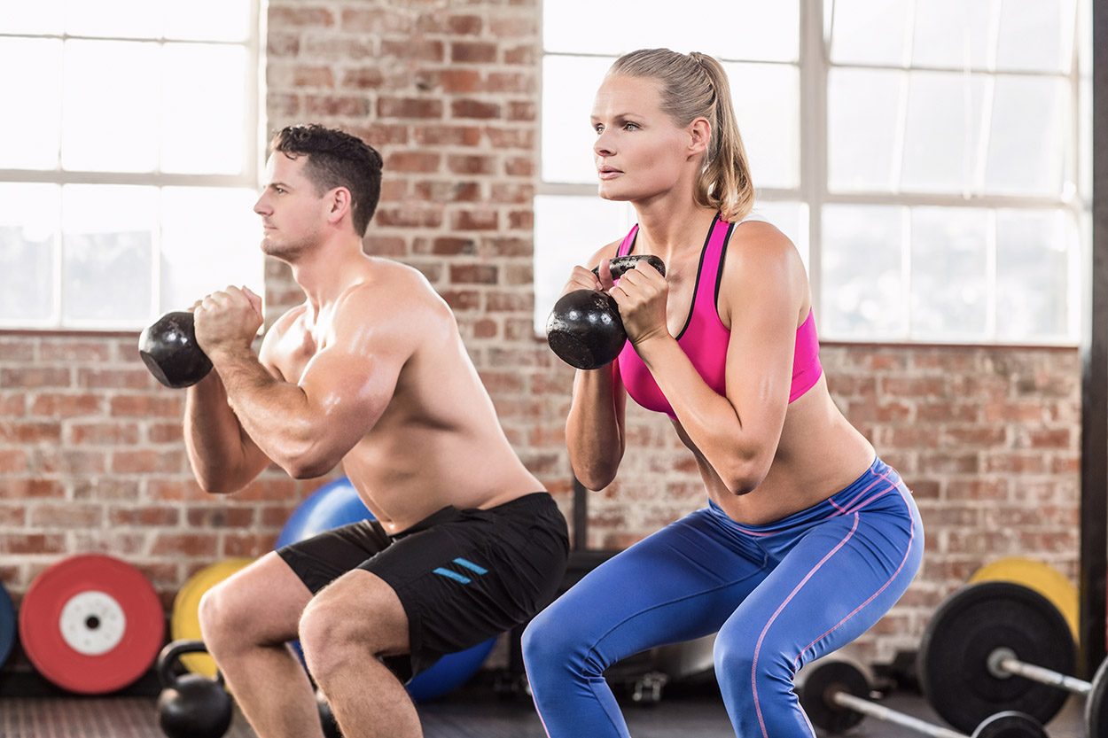 Man and woman doing kettle bell exercises