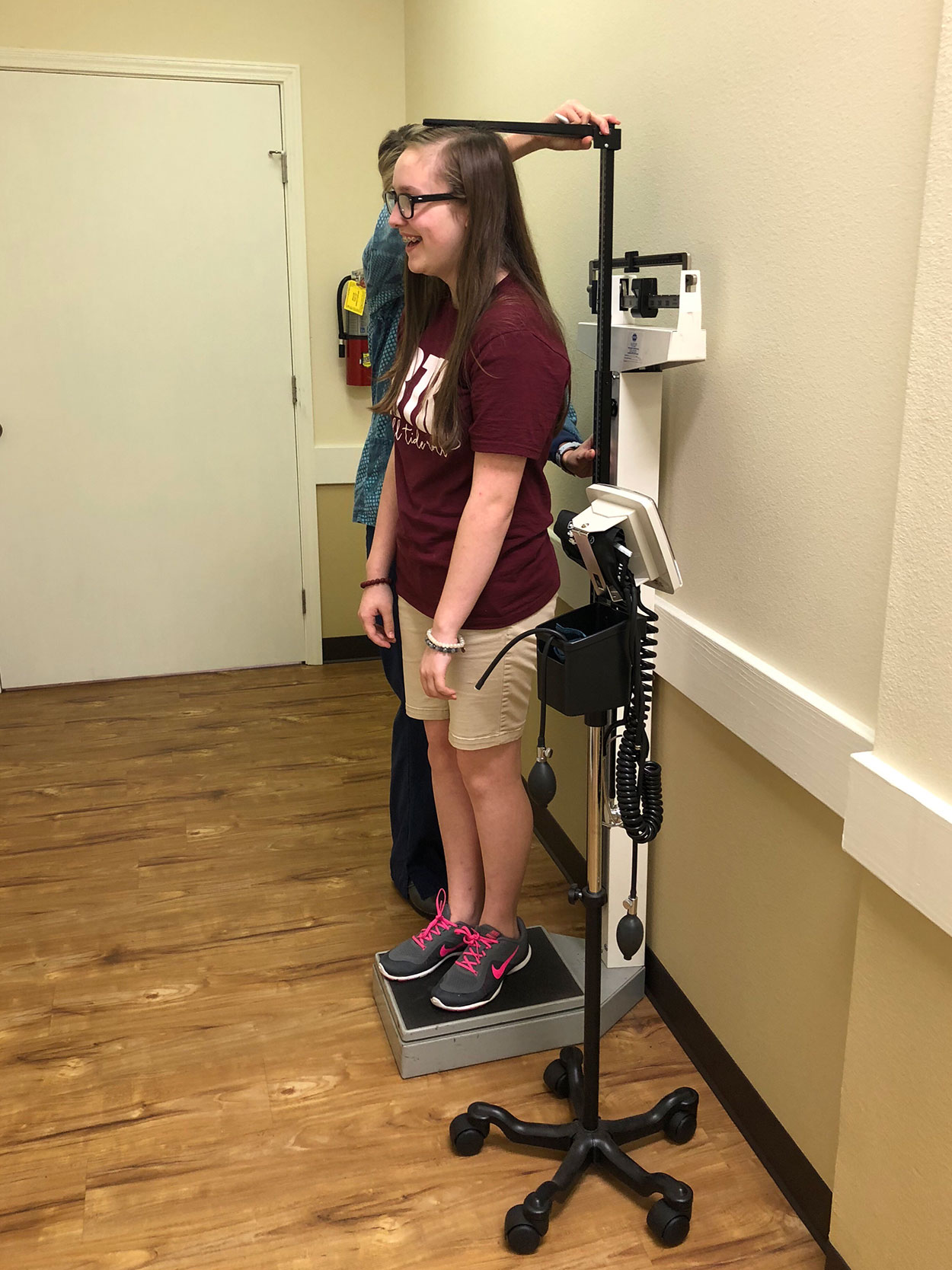 Nurse Measuring the Height of a Teenage Girl.