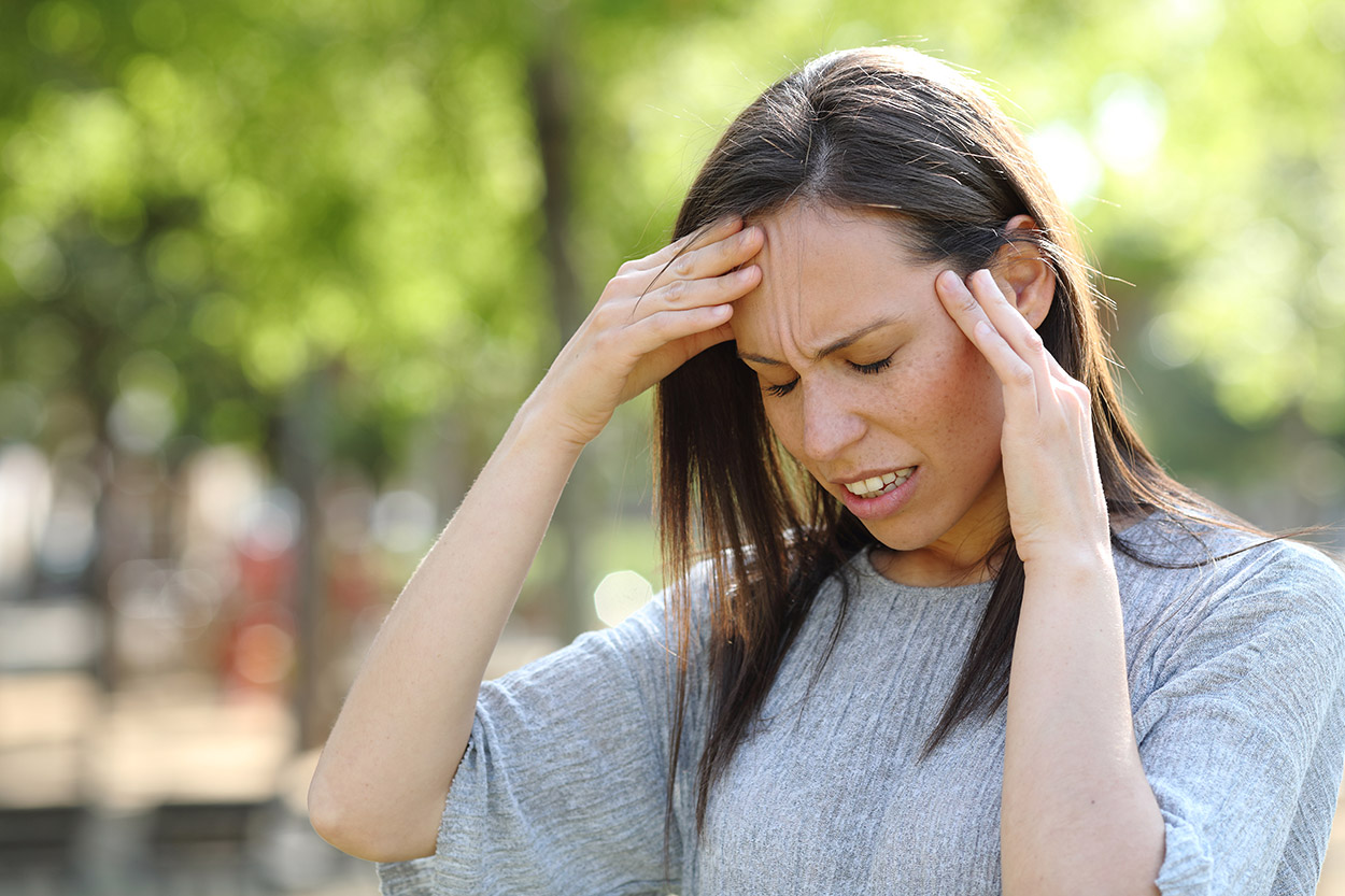 Woman having a migraine outside