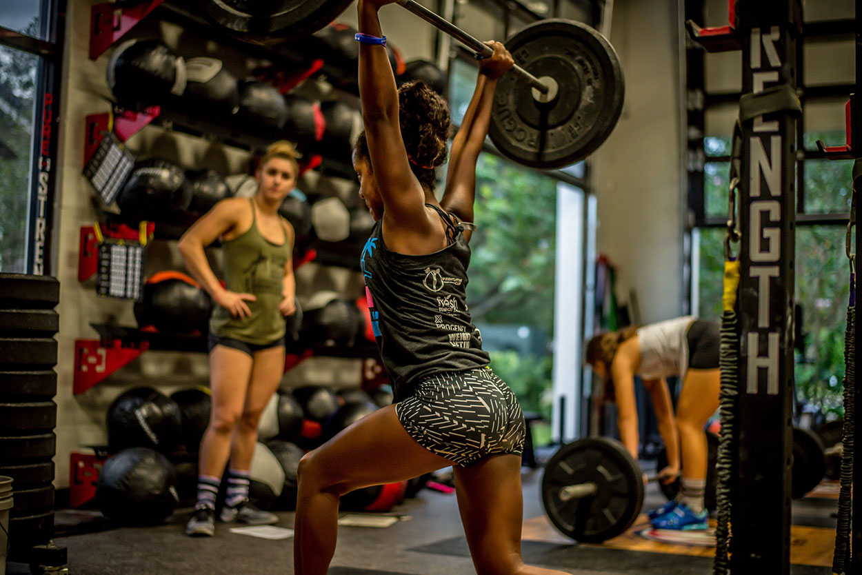 Woman Lifting a Barbell in the Gym.